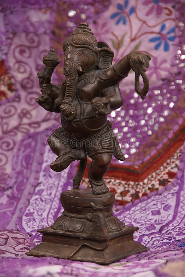 Bronze Ganesha dancing. On purple Rajasthani textile backdrop made from saris. [Ganesha, the son of Shiva and Parvati, the elephant headed god, is worshipped stock images