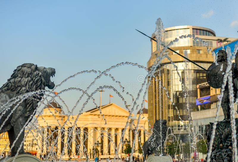 Bronze historical statues surrounded by spray and water jets,Skopje,Macedonia. SKOPJE/NORTH MACEDONIA-AUGUST 28 2018:Water jets,statues and spray at main stock photo