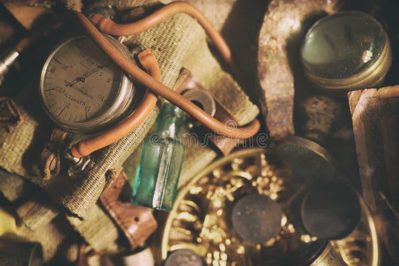 Bronze jewelry, old money, retro manometer, magnifier, glass bottle, silverware. Vintage. Different antique items on the table: bronze jewelry, old money, retro royalty free stock photos