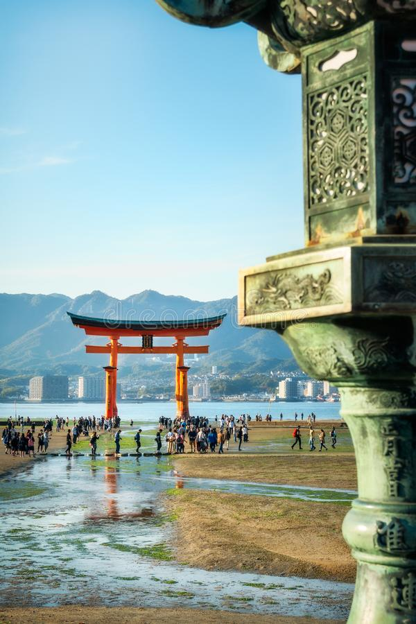 Bronze lantern detail with the famous Torii Gate in the background, Miyajima Island, Japan. Miyajima Island, Hiroshima Bay, Japan -November 7, 2018: The famous stock image