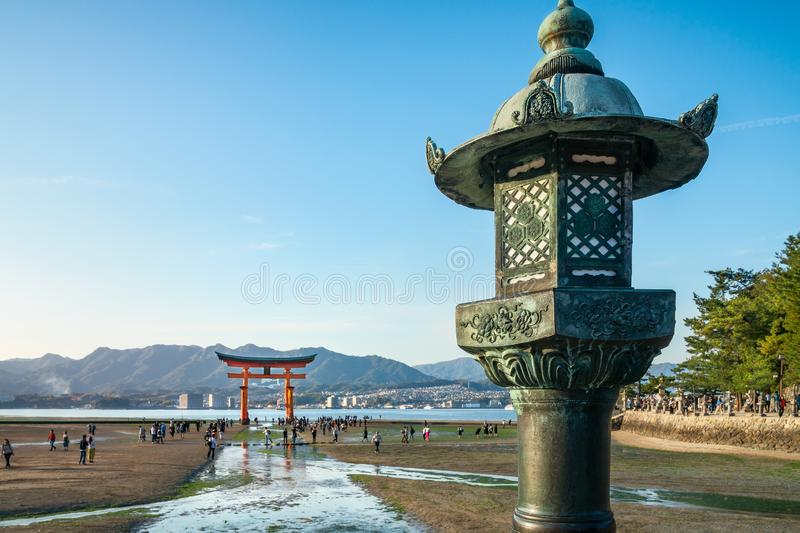 Bronze lantern with the famous Torii Gate in the background, Miyajima Island, Japan. Close-up of a decorated bronze lantern with the famous Torii Gate in soft stock images