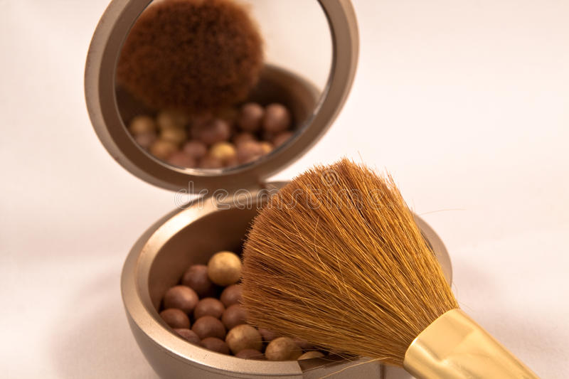 Bronze make-up pearls. With brush stock image