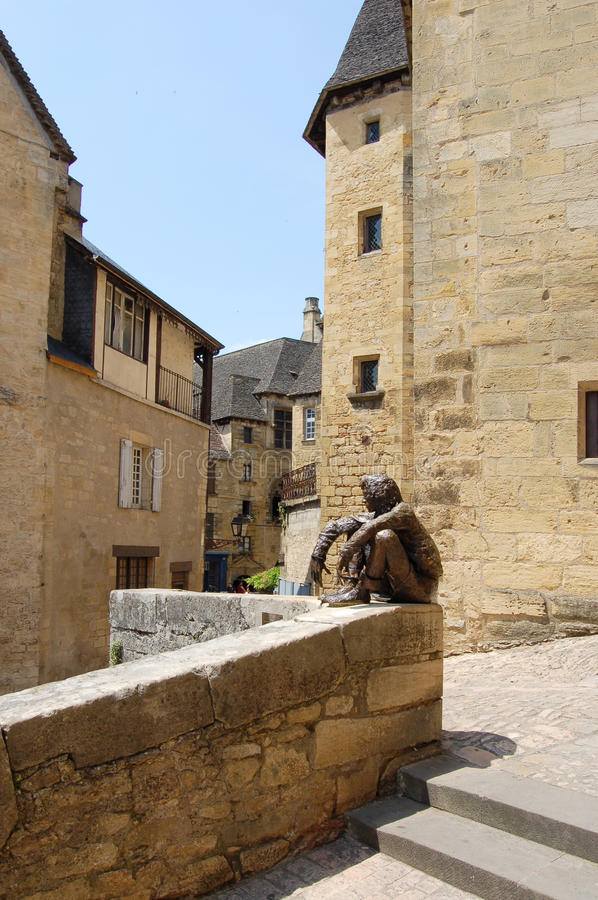 Bronze man on a wall at Sarlat. A bronze statue of a sitting man on a wall at Sarlat, France royalty free stock image
