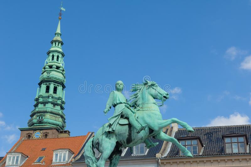 Copenhagen, Equastrian statue of Absalon and tower of Nicolai Church, Hojbro Square, Copenhagen, Denmark. Bronze monument of Absalon, founder of the City royalty free stock photos