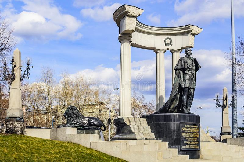 Bronze monument to the Russian emperor Alexander the Second - the Liberator and near a bronze lion-symbol of royal power. royalty free stock image