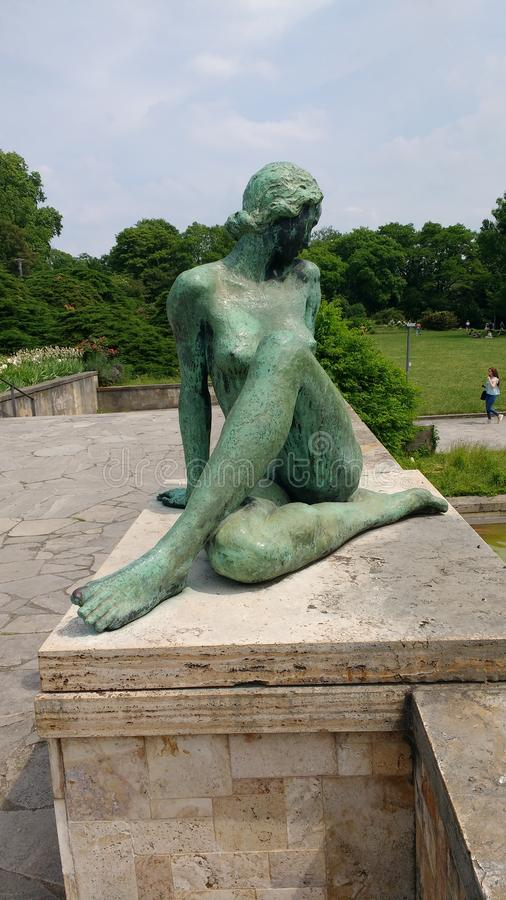 Bronze nude Art Nuveau. Figure overlooking pond in Franfurt am Mains Goethe University. A very sunny summers day royalty free stock images