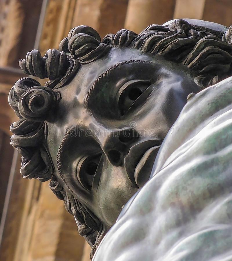 Bronze Perseus Statue Close Up Face Gazes Down at Camera. Bronze Antique Statue Close up Face of Perseus Gazes at Camera from Piazza in Florence Italy stock photos