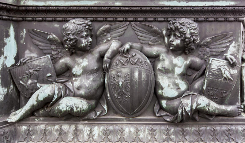 Bronze relief. Of cherubs holding shields stock photos