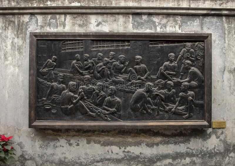Bronze relief in Hoa Lo Prison, commemorating turning the prison into a school to propagate the revolutionary argument royalty free stock photo