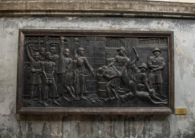 Bronze relief of Vietnamese prisoners in Hoa Lo Prison struggling against the terrorism of the French royalty free stock images