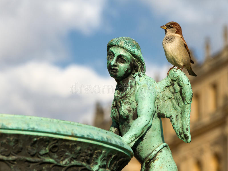 Bronze sculpture angel sparrow. Old historical bronze sculpture of angel man in the Versailles palace park closeup with the palace fasade as a background and royalty free stock photo