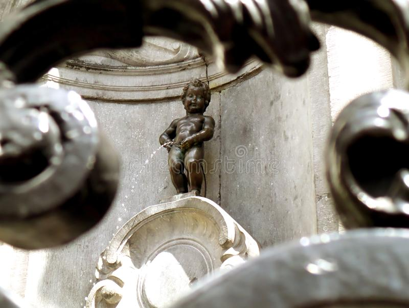 Bronze Sculpture of Manneken Pis as View Through the Iron Fence, a Small but Famous Landmark of Brussels. Of Belgium stock images