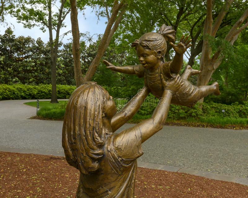 Bronze sculpture of woman holding up a happy child by Gary Price at the Dallas Arboretum and Botanical Garden royalty free stock images