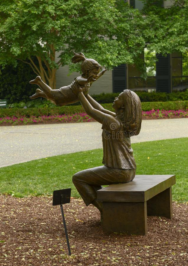 Bronze sculpture of woman holding up a happy child by Gary Price at the Dallas Arboretum and Botanical Garden. Pictured is a Bronze sculpture of a woman holding royalty free stock image