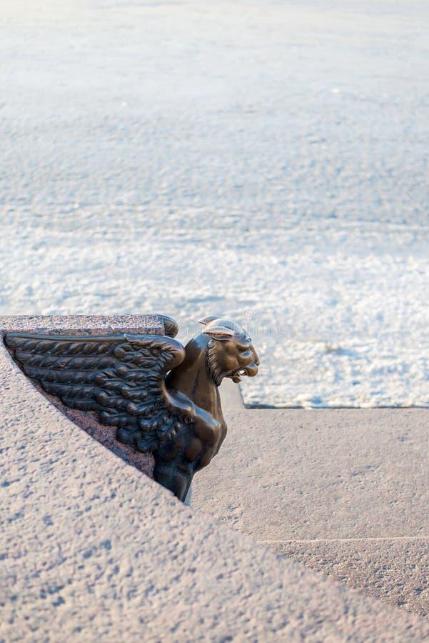 Bronze sculptuur van een Griffin op een wazig achtergrondtextuur van de dijk en sneeuw royalty-vrije stock foto's