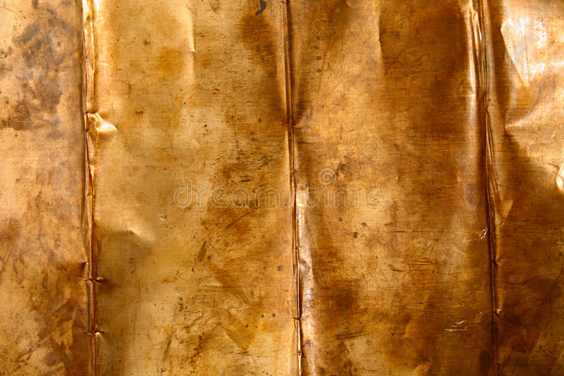 Bronze sheet metal. Abstract background from crumpled bronze sheet metal stock photo
