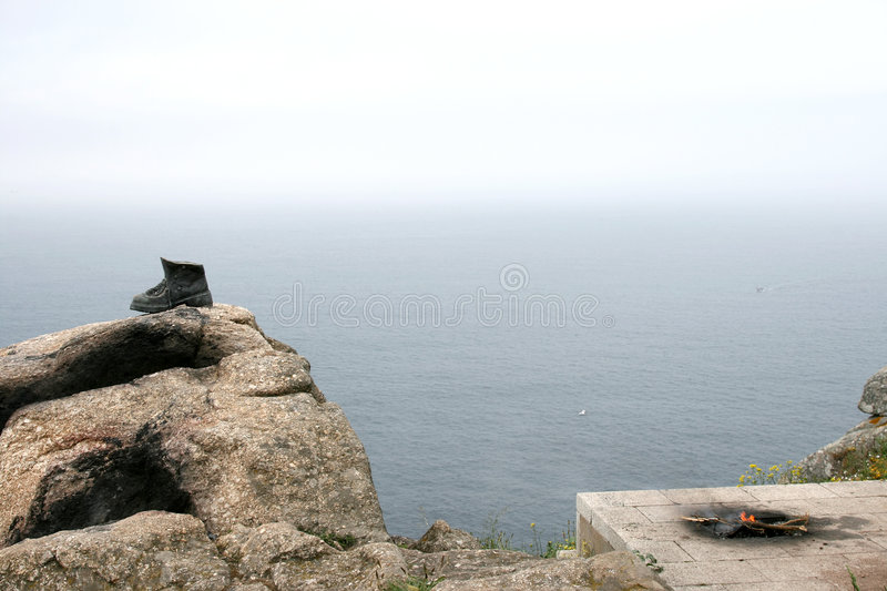 A bronze shoe as symbol for pilgrimage in Spain. Cape Finisterre or Fisterre is a rock-bound peninsula on the west coast of Galicia in Spain and the final stock photo