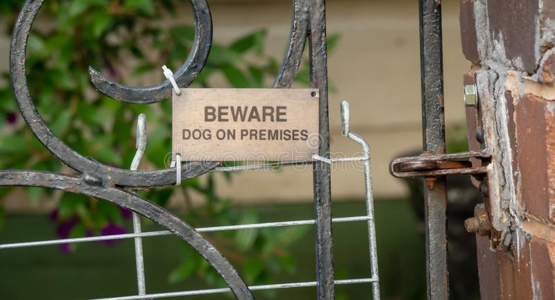 Bronze sign BEWARE DOG ON PREMISES on old gate royalty free stock images