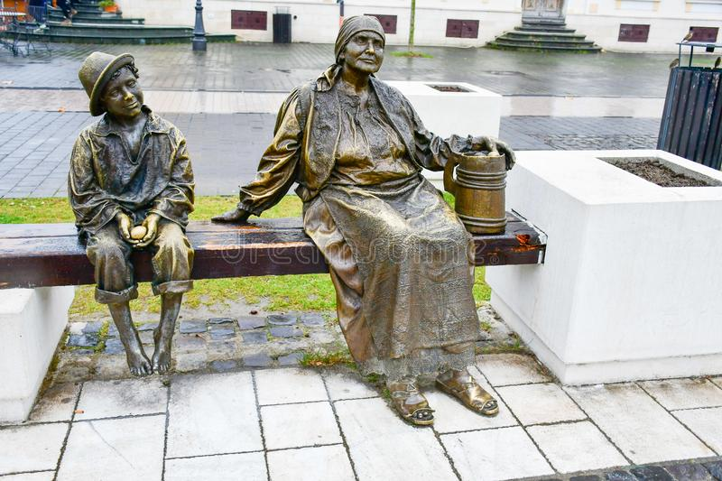 Bronze statue of barefoot child and grandmother stock photo