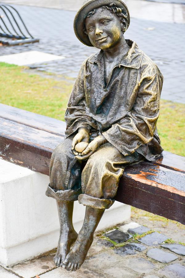 Bronze statue of barefoot child holding egg royalty free stock photo