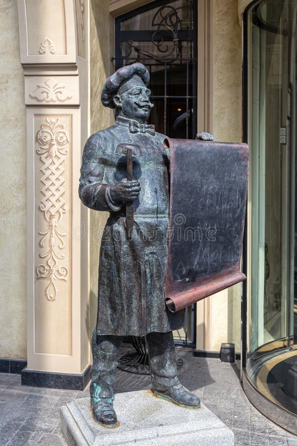 Bronze statue of a chef with a ladle and a scroll of menus in his hands, at the entrance to a restaurant in Tbilisi royalty free stock photography