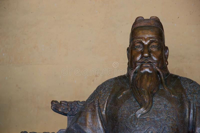Bronze statue of Chinese man with hat and beard royalty free stock image