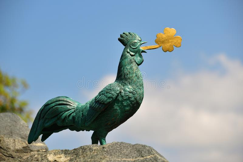 The bronze statue of a cock with golden cloverleaf in its beak. HAHNENKLEE, GOSLAR, LOWER SAXONY, GERMANY - JUNE 22, 2019: The bronze statue of a cock with stock photo