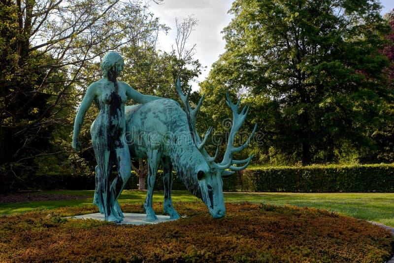 Bronze statue deer woman, Arboretum Park, Wespelaar, Leuven, Belgium. Bronze statue of a deer and woman in the Arboretum Park in summer, Wespelaar, Leuven royalty free stock images