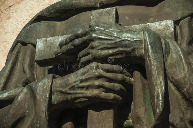 Bronze statue detail of priest hands holding a cross at Caceres. Bronze statue detail of priest hands holding a cross on the corner of the Santa Maria Cathedral stock images