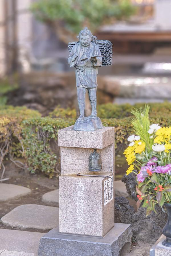 Bronze statue of economist Ninomiya Kinjiro with at its base a japanese sutra and a bronze bell Bonshō. Tabata, Japan - January 03 2019: Bronze statue of stock photos