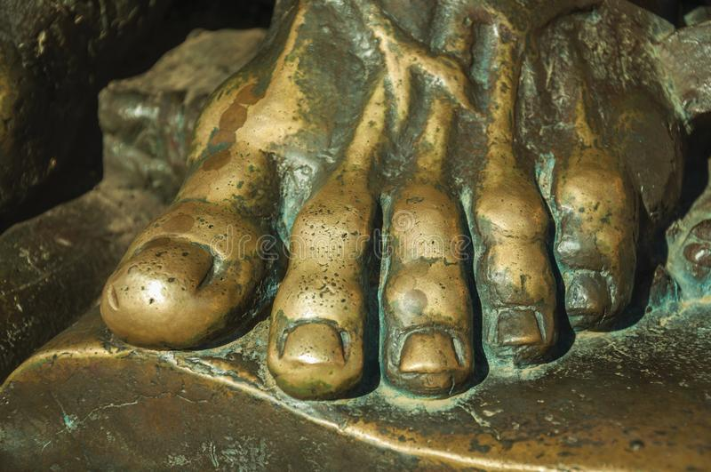 Bronze statue of foot over an open book at Caceres. Bronze statue detail of foot from priest over an open book on the corner of the Santa Maria Cathedral at royalty free stock images