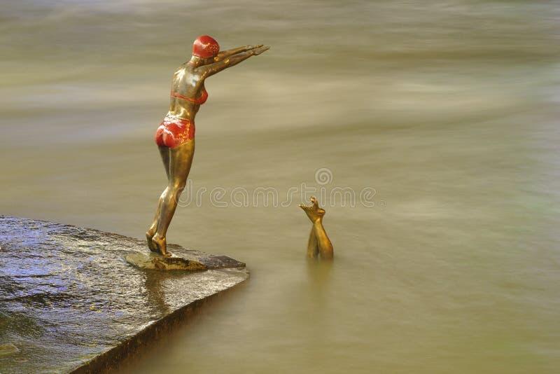 Bronze statue of girl swimmer jumping in Vardar stock photography