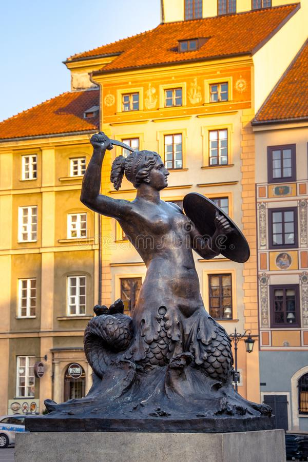 The bronze statue of Mermaid on the Old Town Market Square of Warsaw, surrounded by colorful old houses, Poland stock photo