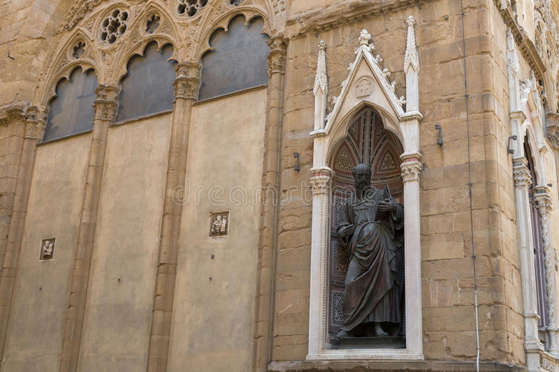 Bronze statue of St. John the Evangelist, detail of Orsanmichele church exterior, niche figures in Florence, Italy. FLORENCE, ITALY - SEPTEMBER 2016 : Bronze royalty free stock photo