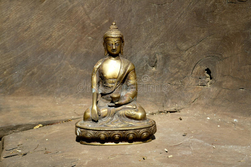 Bronze statue of Touching earth Buddha on wood royalty free stock photography