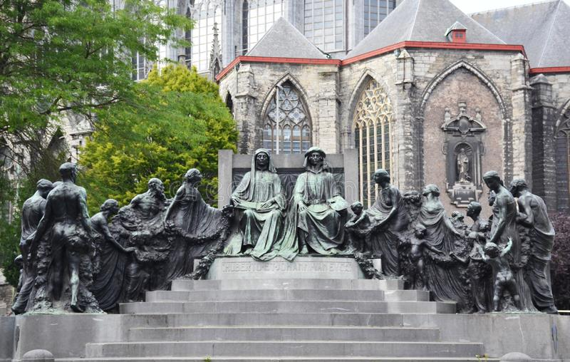 Bronze statue of Van Eyck brothers - Hubert and Jan with St. Bavo`s cathedral on the background stock photo