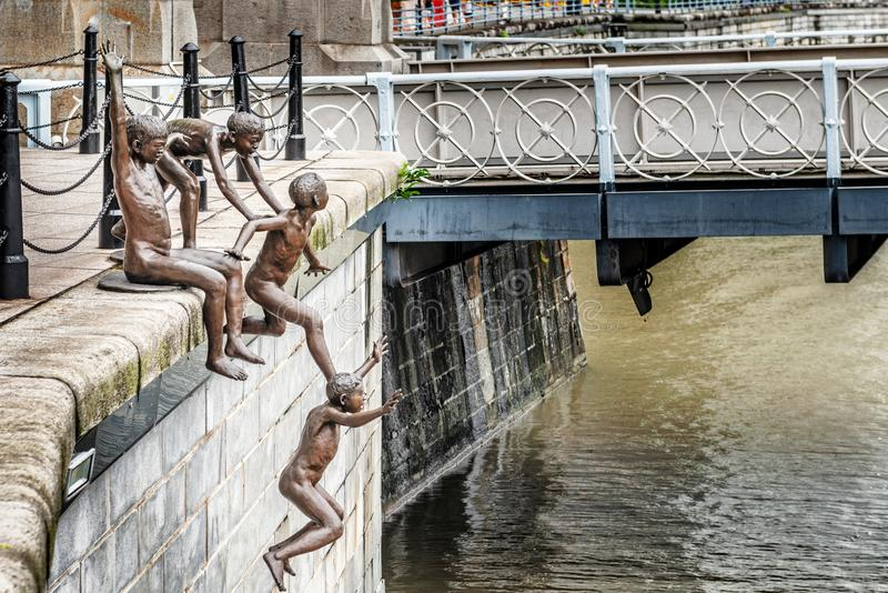 Bronze statues of children jumping into the river in Singapore. Singapore - Jan 14, 2018: People of the River, bronze statues by Chong Fah Cheong of children royalty free stock photo