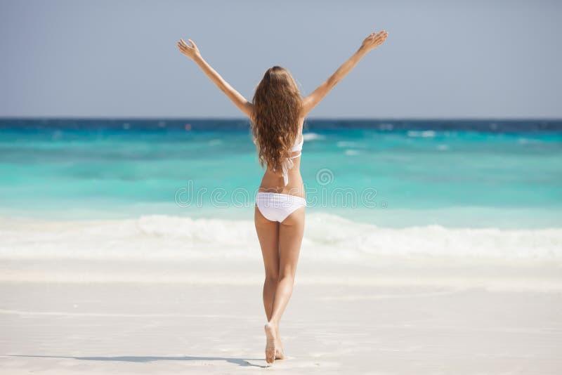 Bronze-Tan Woman Sunbathing At Tropical-Strand stockfotos