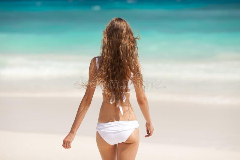 Bronze-Tan Woman Sunbathing At Tropical-Strand stockbild