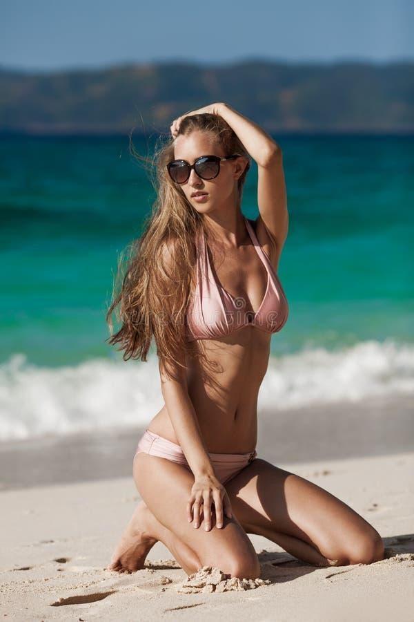 Bronze-Tan Woman Sunbathing At Tropical-Strand stockbilder