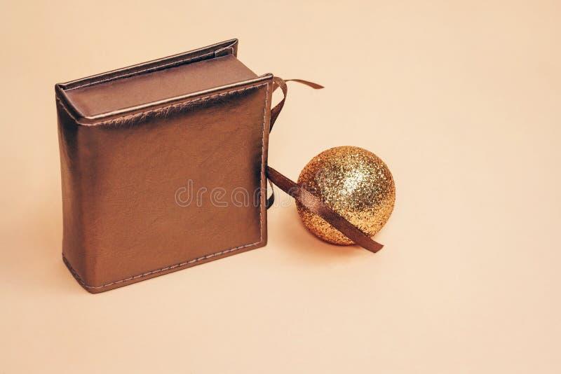 Bronzefarbiger Präsentkarton des Retrostils mit einem Seidenbogen allein mit Goldfunkelndem Weihnachtsball auf Pastellhintergrund stockfoto