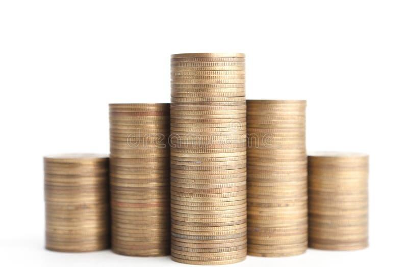 Bronzeie moedas estão verticalmente nas colunas, isoladas imagem de stock