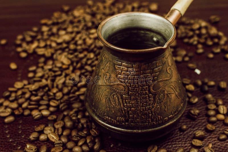 Bronzekaffee Türke und Kaffeebohnen Hintergrund stockbilder