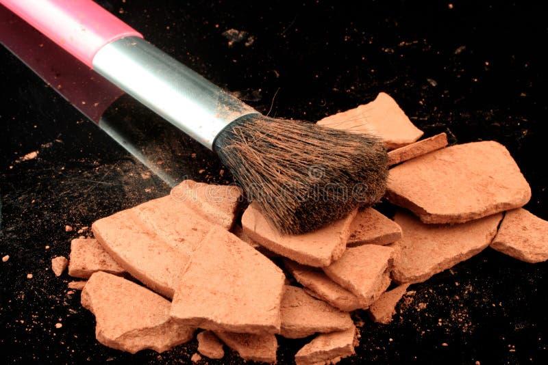 Bronzer and brush. Broken up facial bronzer powder and brush royalty free stock photo