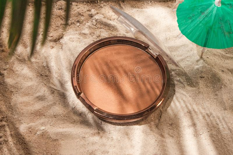 Bronzer in the form of a cushion on the sand. With an umbrella and a palm branch. the shadows of the palm branches stock photos