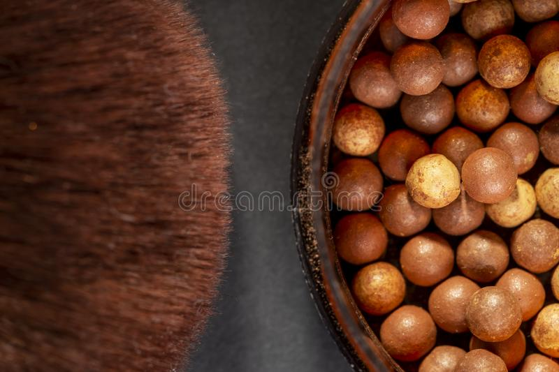 Bronzer and a make up brush. Close up of face powder pearls in an open powder box and a make up brush. Feminine cosmetics and make up product, bronzer and royalty free stock photography