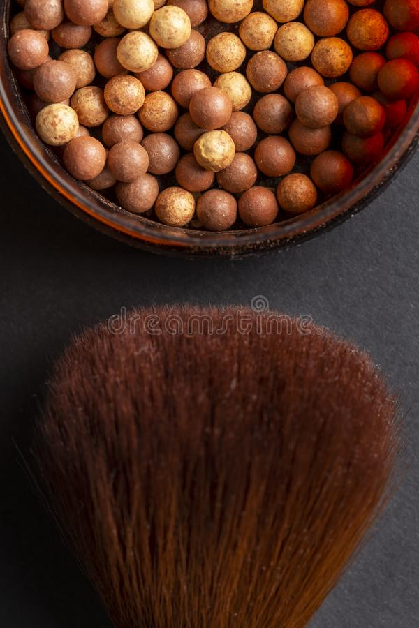 Bronzer and make up brush. Table top shot of face powder pearls in an open powder box and a make up brush. Feminine cosmetics and make up product, bronzer and royalty free stock image