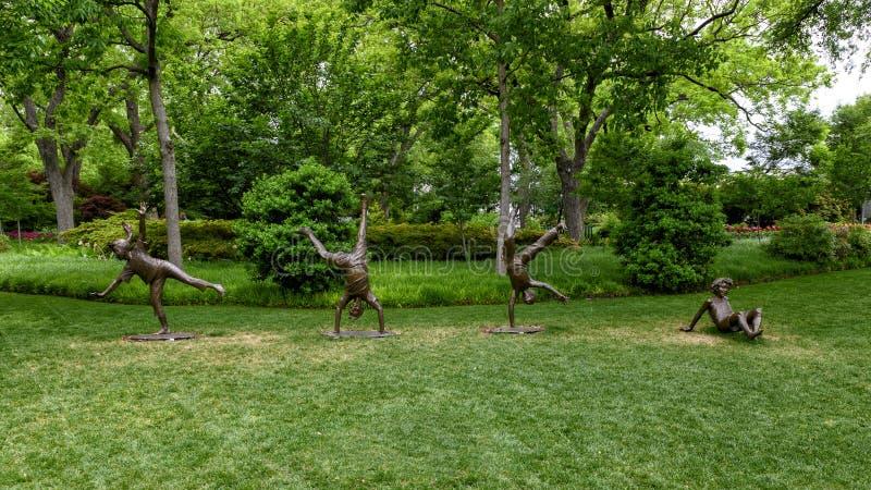 Bronzeskulptur, die von den Kindern tun Wagenräder durch Gary Price an Dallas Arboretum und am botanischen Garten ist stockfotos
