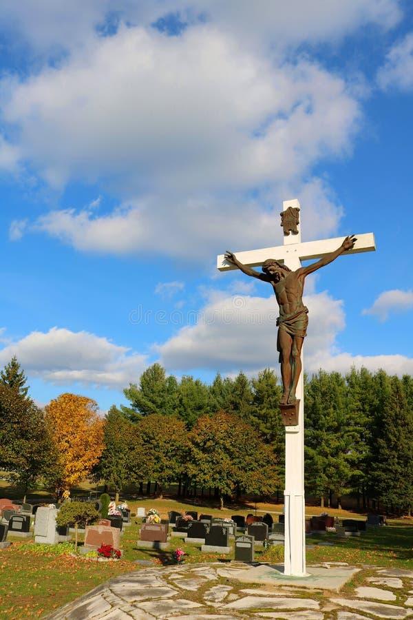 Bronzeskulptur von Jesus Christ auf weißem hölzernem Kreuz am Kirchhof stockbilder