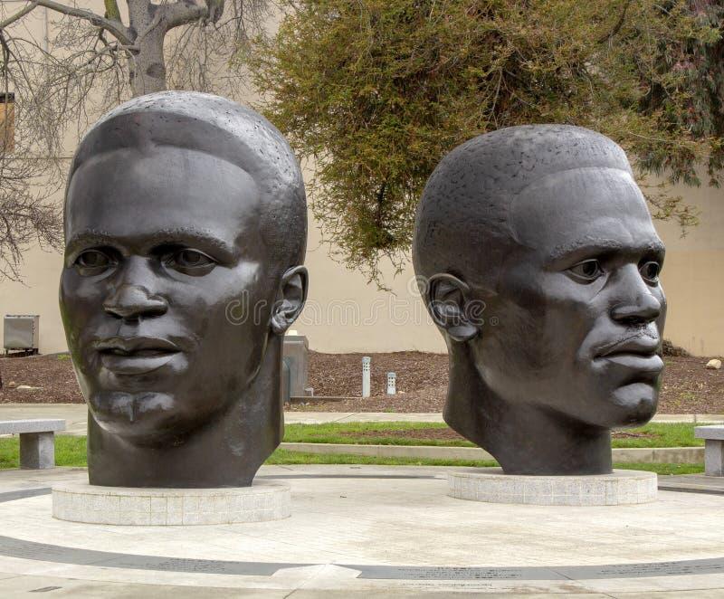 Bronzeskulpturen von Köpfen des Regenmantels und von Jackie Robinson stockfotografie